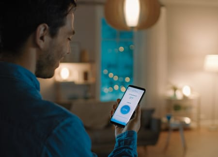 Man using smart home app to control lights