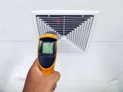 HVAC technician checking the temperature of an air supply register