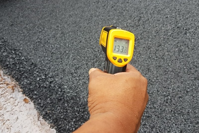 IR thermometer measuring temperature of asphalt